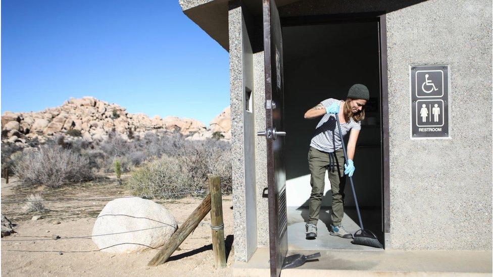 Una voluntaria limpia un baño en el parque nacional Joshua Tree de California