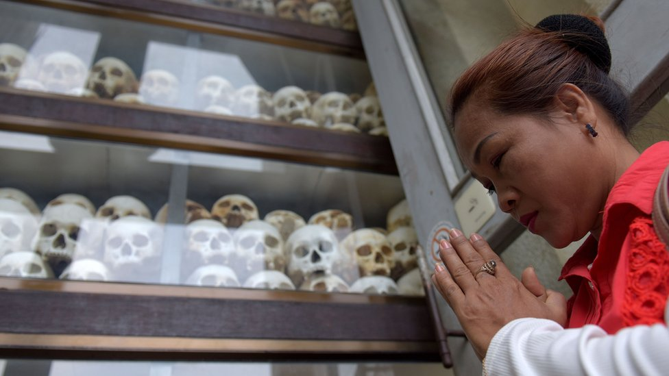 A woman prays in front of skulls of Khmer Rouge victims at the Killing Fields