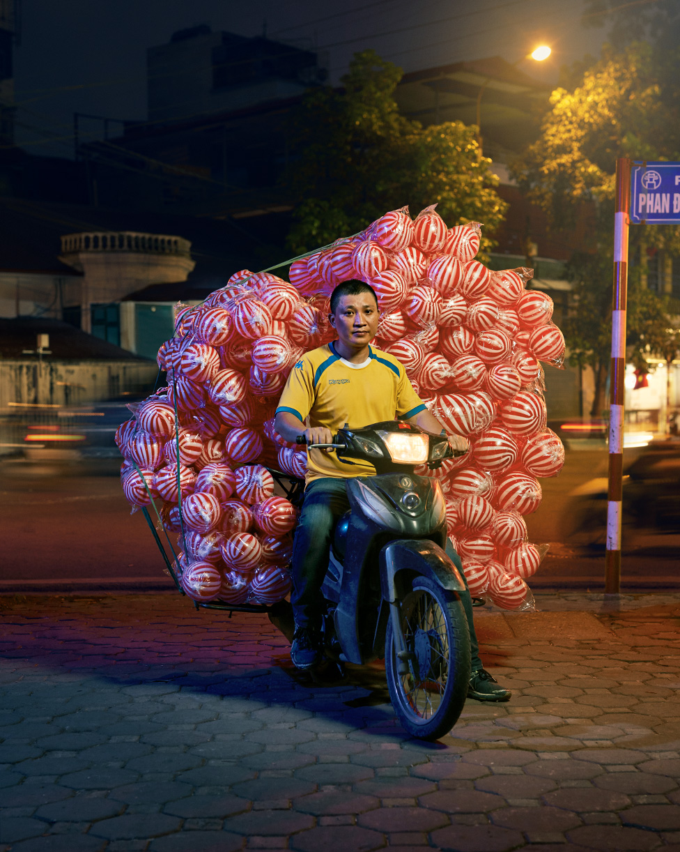 A man posed on a motorcycle with hundreds of red and white coloured bouncy attached to the back