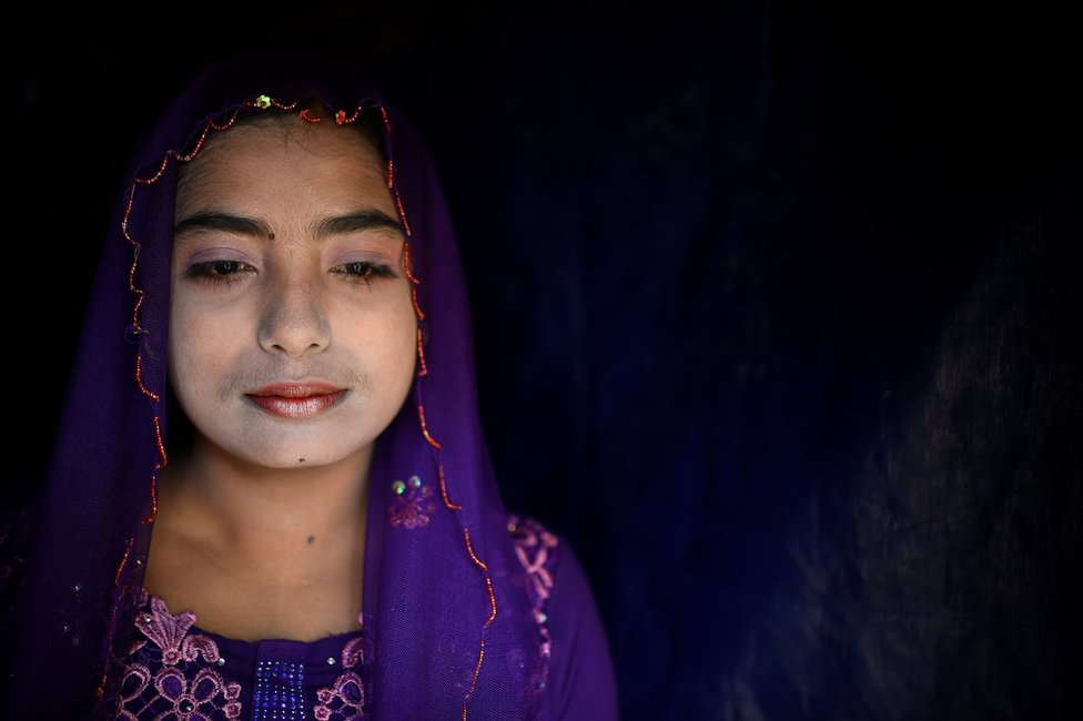Rohingya refugee Toyuba, aged 18, poses for a photograph as she wears thanaka paste at Kutupalong camp in Cox's Bazaar, Bangladesh