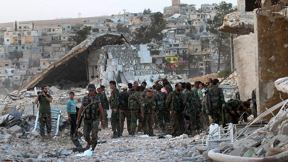Syrian government forces walk through the Handarat Palestinian refugee camp, north of Aleppo, on 2 October 2016