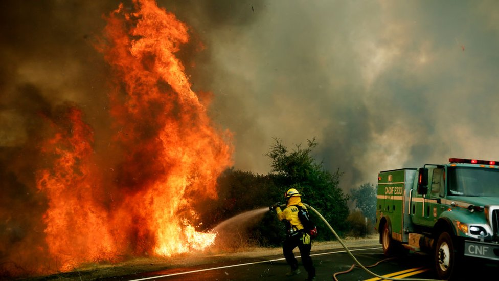 Fire fighters spray water on a wildfire in California