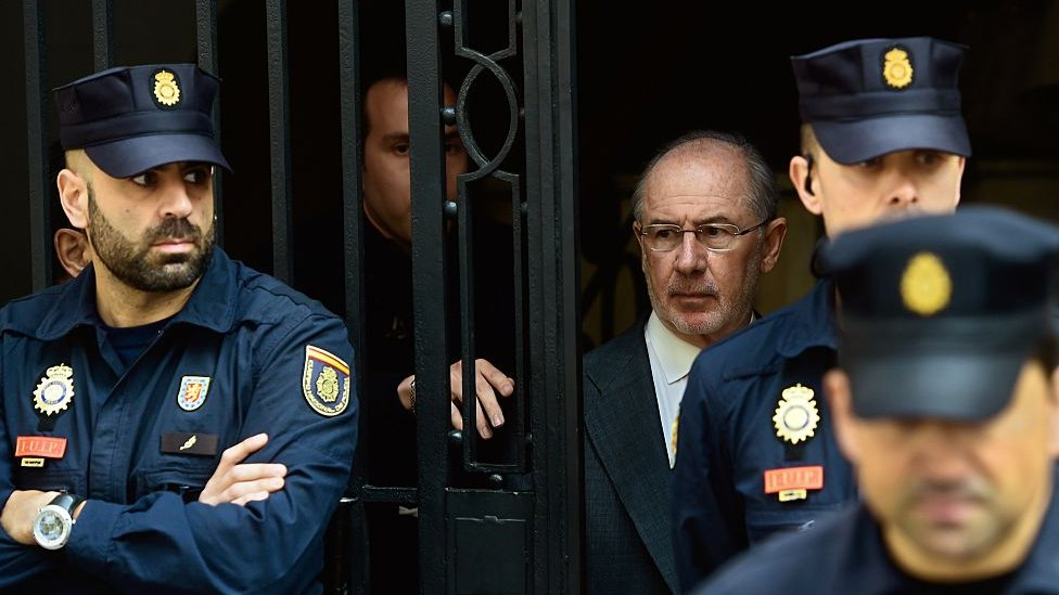 Former IMF head and former Spanish Economy minister Rodrigo Rato (C) is surrounded by policemen as he leaves his office, on 17 April 2015 in Madrid