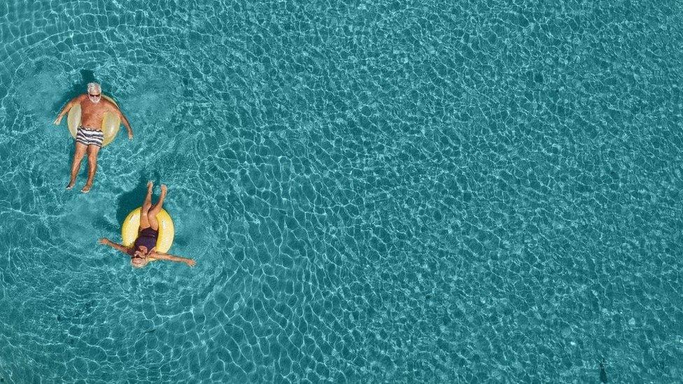 Una pareja adulta flotando en una piscina