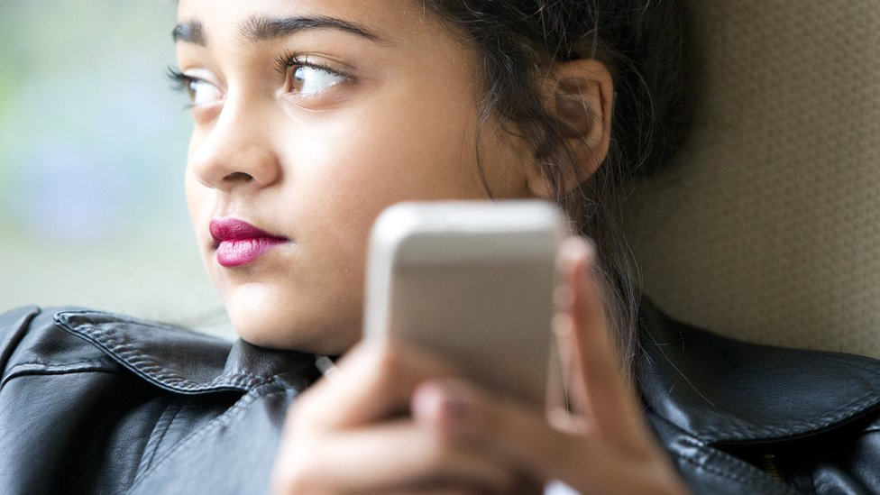 File photo: A young girl holding a mobile phone