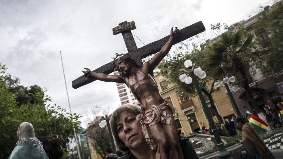 Mujer porta un crucifijo durante las protestas en Bolivia.