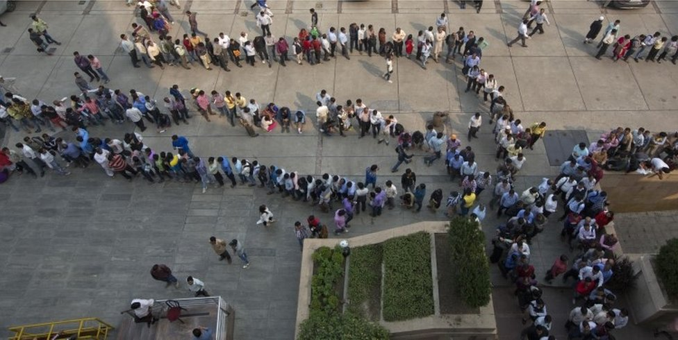 Indians stand in queues to exchange or deposit discontinued currency notes outside an Axis Bank branch in central New Delhi, India.