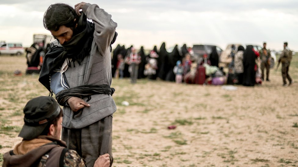 A man suspected of being an Islamic State (IS) group fighter is searched by a member of the Kurdish-led Syrian Democratic Forces (SDF) after leaving the IS group's last holdout of Baghouz, in Syria's northern Deir Ezzor province on February 27, 2019