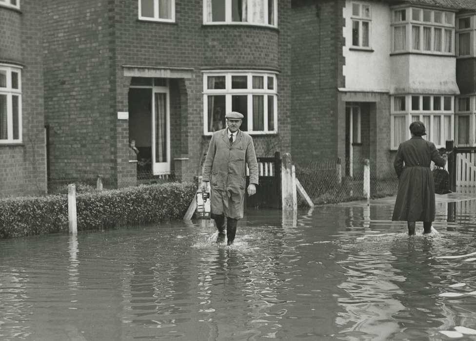 Milkman delivers during a flood