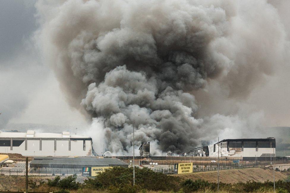 El humo se eleva desde un edificio de Makro incendiado durante la noche en Umhlanga, al norte de Durban, el 13 de julio de 2021.