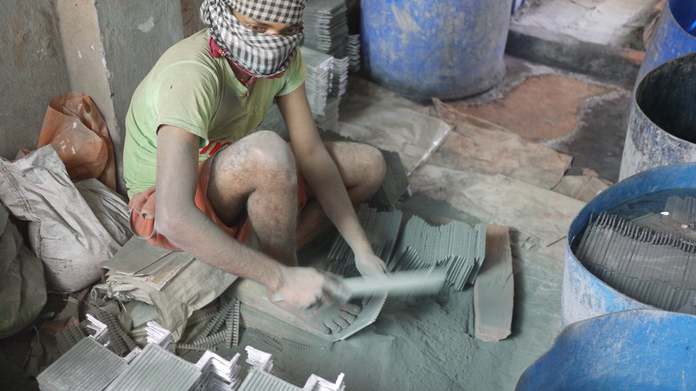 A worker at an informal recycling place clearing lead dust from battery parts