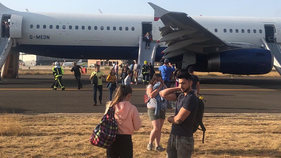 Passengers disembarking via emergency chute from the flight in Valencia