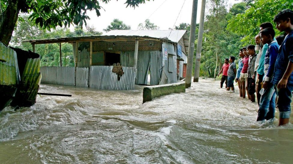 Bystanders watch floodwaters rage near a house in Kurigram, northern Bangladesh.