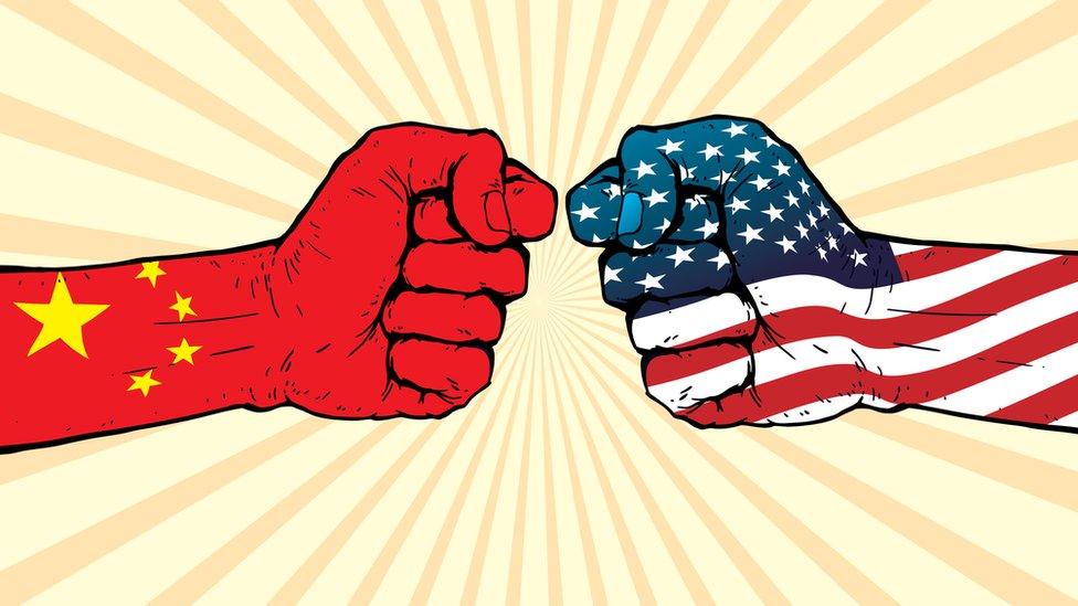 Dos puños, uno con la bandera de Estados Unidos y otro con la china, pegándose el uno al otro.