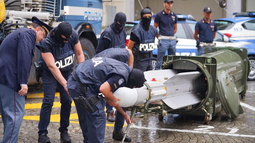 Italian police with missile seized in raids on far-right groups