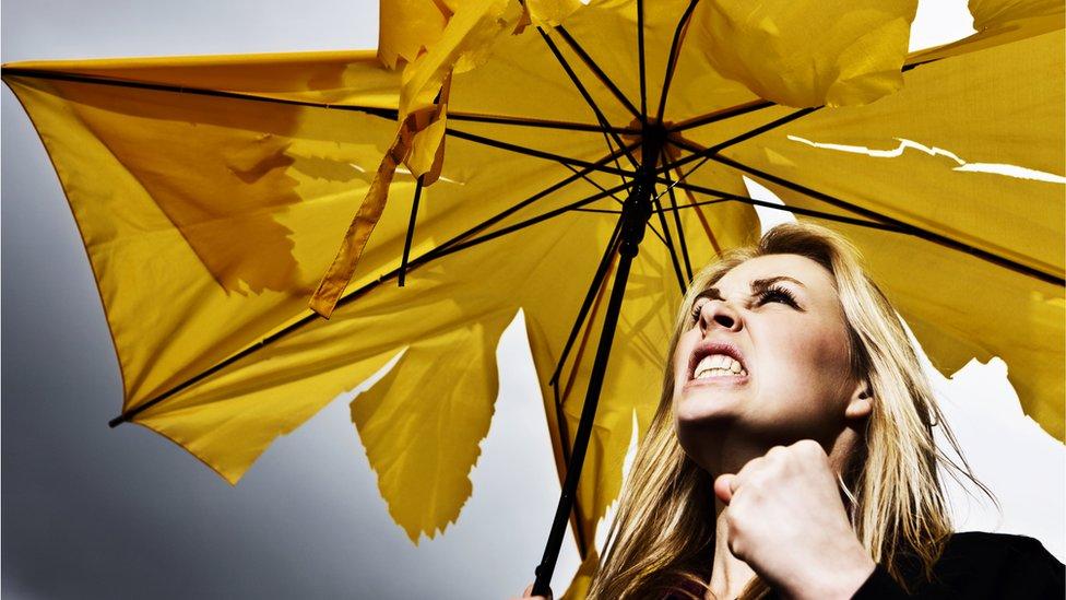 Una mujer enojada con un paraguas amarillo roto bajo la lluvia.