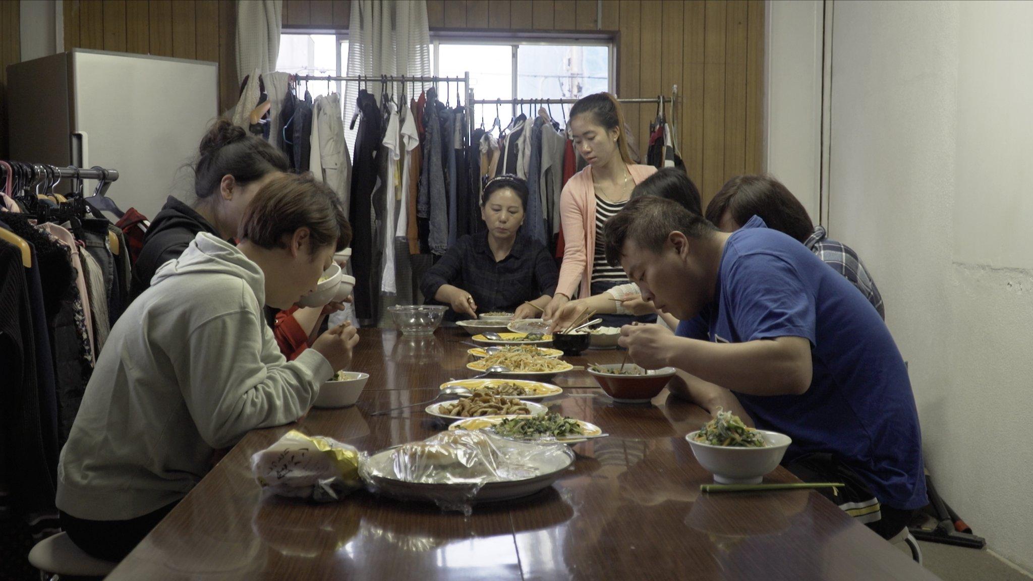 Buruh migran dari Asia di sebuah tempat penampungan di Jepang, duduk sambil makan malam bersama.