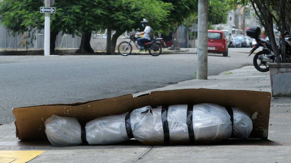 An abandoned corpse wrapped in plastic and covered with cardboard lies on the pavement in Guayaquil, Ecuador, 6 April 2020