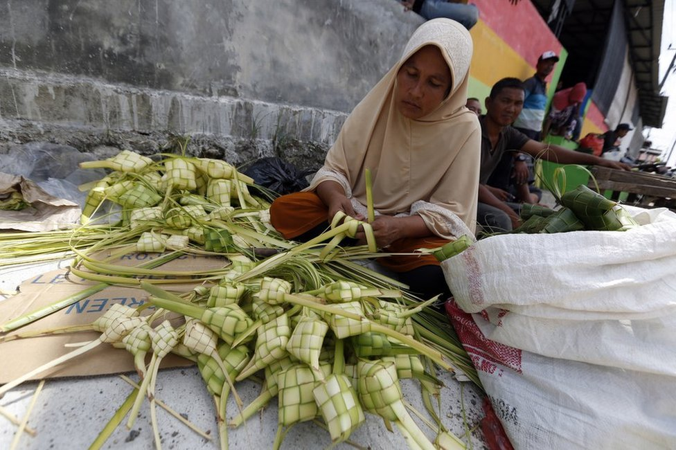 An Acehnese woman prepares ketupat, a type of rice dumpling packaged in palm leaves, in the lead up to Eid al-Fitr at a traditional market in Banda Aceh, Indonesia, 13 June 2018