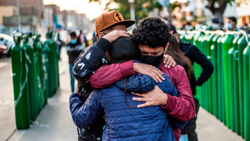 Familiares de pacientes de covid se abrazan frente a bombonas de oxígeno en Callao, Perú