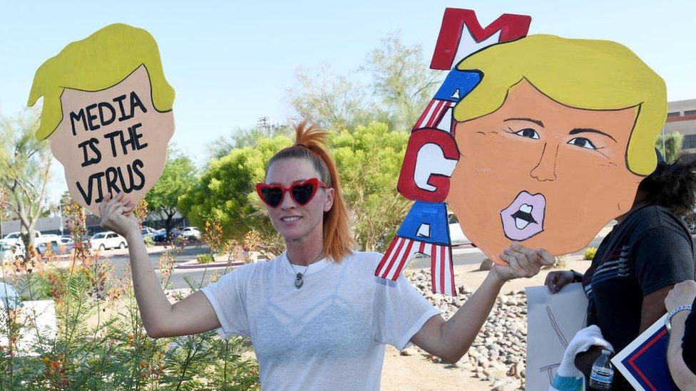 Partidaria de Trump con un cartel crítico con los medios de comunicación.
