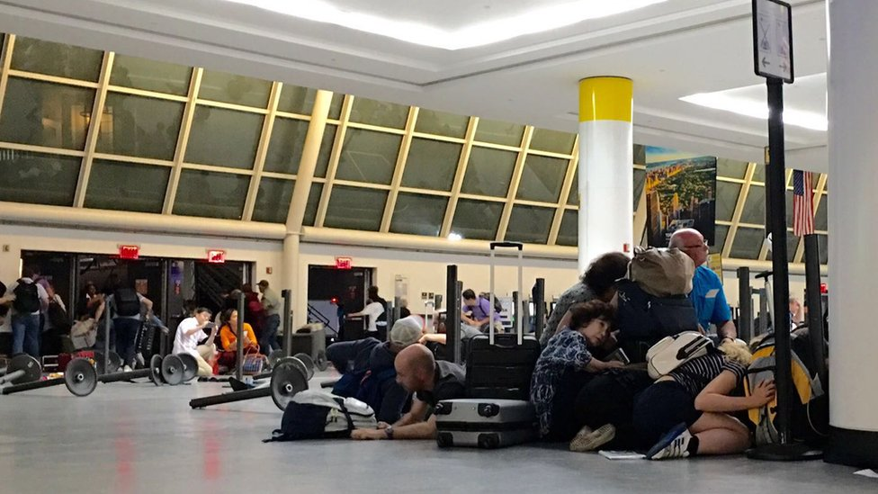 Passengers on the ground in the immigration area of JFK airport, 15 August