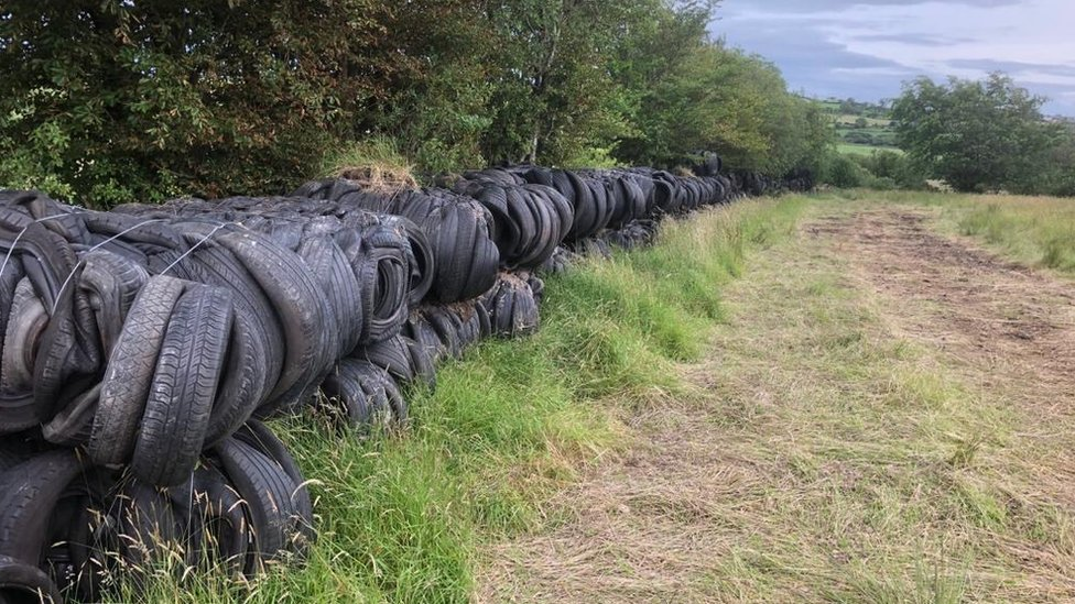 Used tyres lining the side of a field