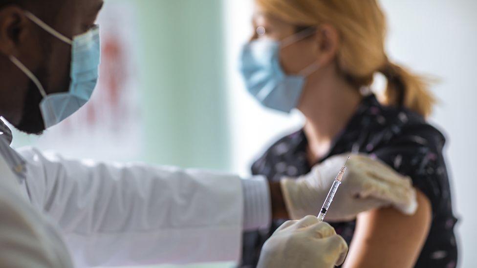 Un médico poniéndole una vacuna a una mujer.