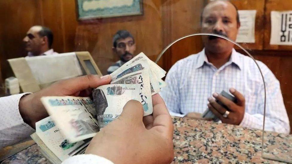 موظف يعد جنيهات مصرية