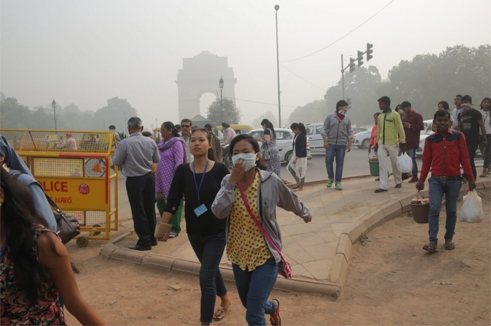 Indian people walk with masks on their faces near the India Gate in New Delhi, India, on 7 November 2016.