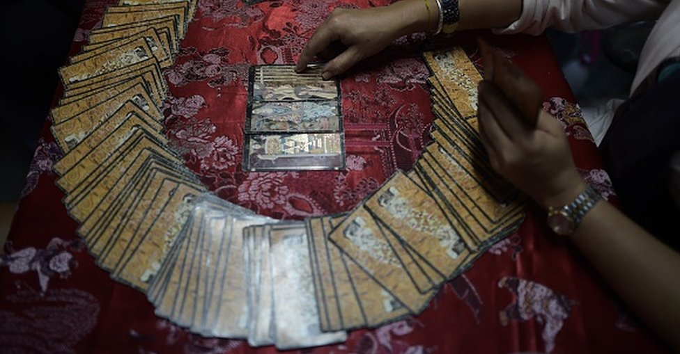 A fortune teller uses tarot cards to predict the future of a woman at a Buddhist temple in Bangkok