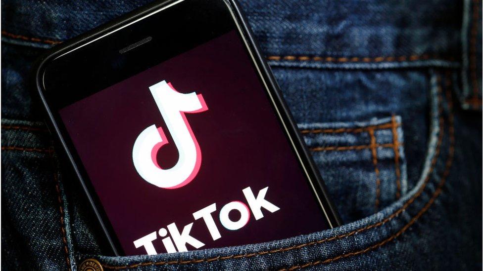 TikTok app on a smartphone sticking out of a pocket