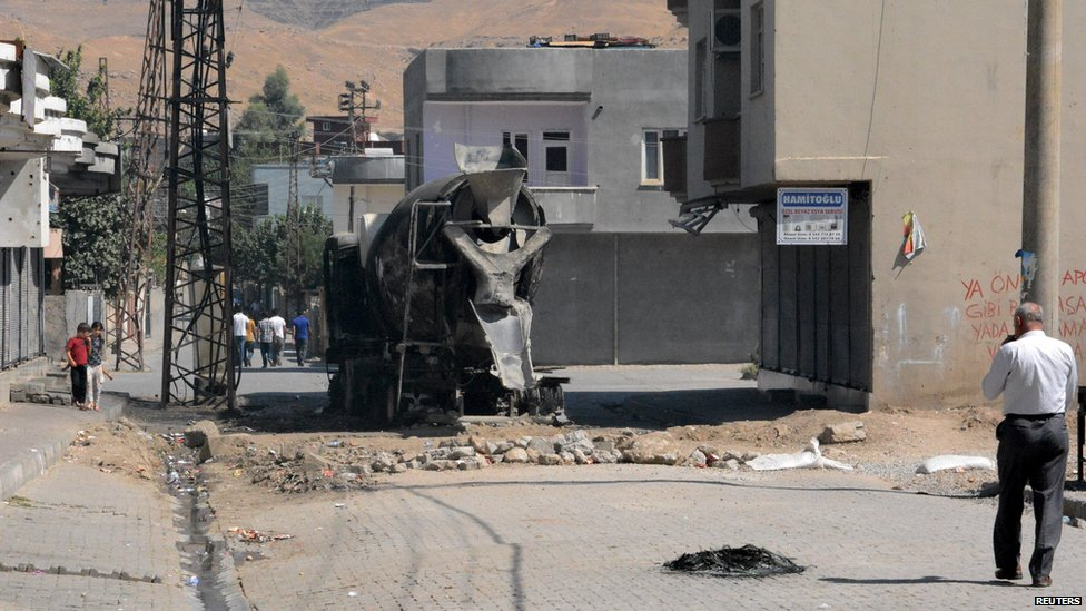 A burned vehicle is seen on a road in town of Cizre in Sirnak province, near the border with Syria, Turkey (28 August 2015)