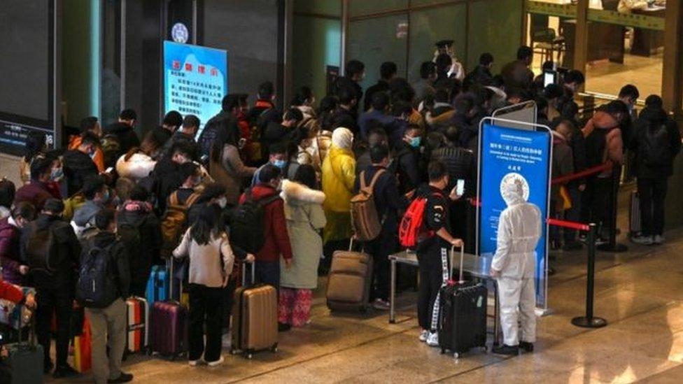 ركاب يرتدون الكمامات ويقفون في الصف في محطة قطارات في ووهان