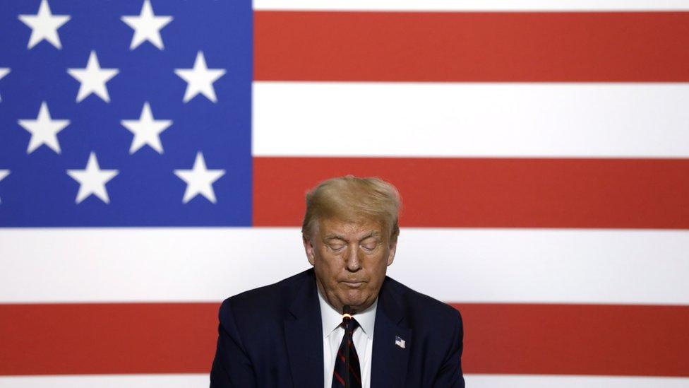 Trump olha para baixo, com bandeira dos EUA ao fundo