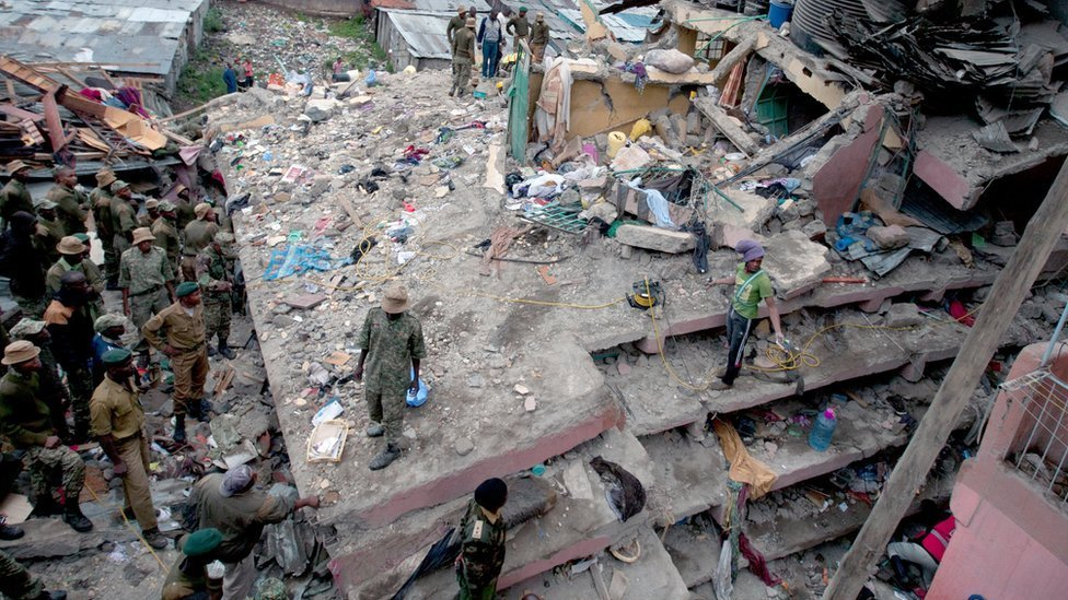 Kenyan police officers and Kenyan National Youth Servicemen work at the site of a building collapse in Nairobi, Kenya, Saturday, April 30, 2016