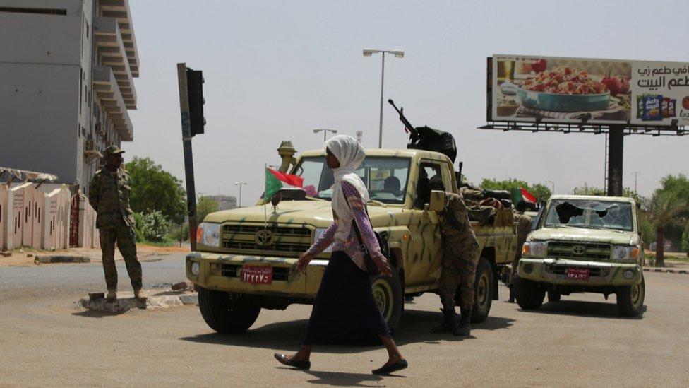 امرأة سودانية تمر من أمام مركبة تابعة لقوات الدعم السريع، يونيو/حزيران 2019