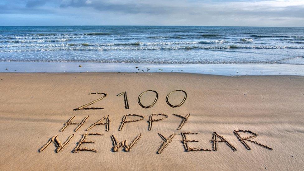 Feliz Año Nuevo 2100 escrito en la arena.