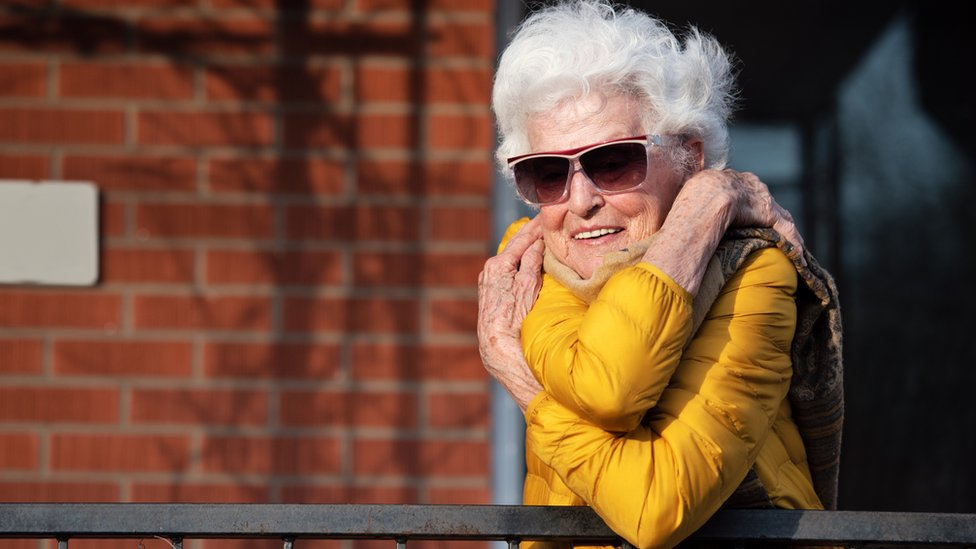 An older lady in isolation hugs herself