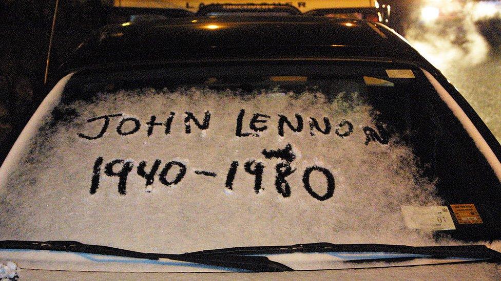 El nombre de John Lennon con su fecha de nacimiento y muerte escrito en la nieve sobre el parabrisas de un auto.