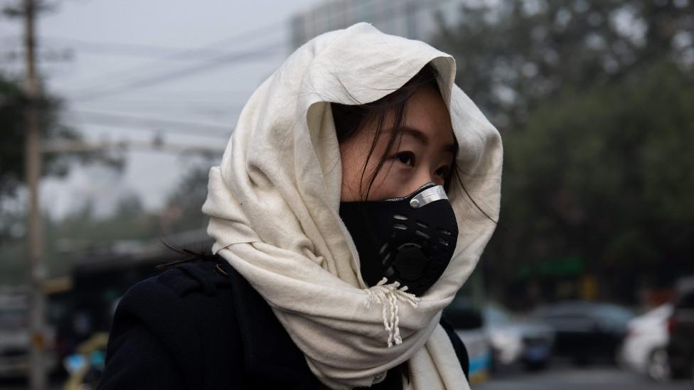 Mujer con una máscara para protegerse de la contaminación en Pekín
