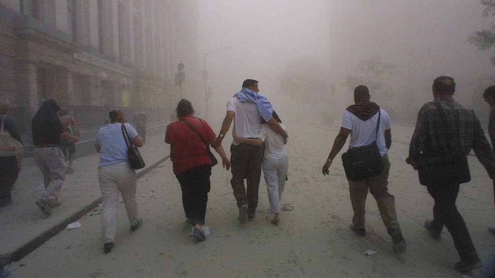 Civilians flee as a tower of the World Trade Center collapses September 11, 2001