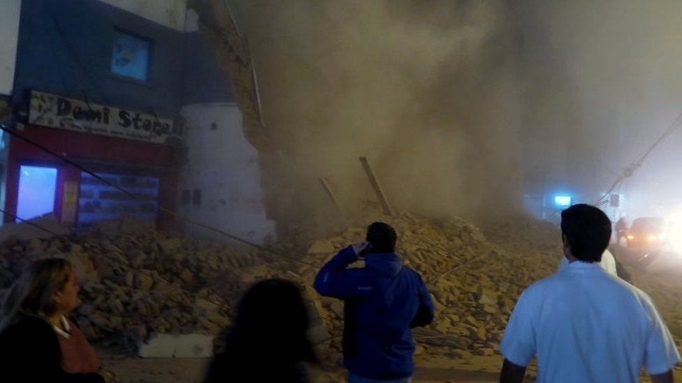 Passers-by stare at the rubble minutes after the collapse of the old Parravicini movie theatre building, in Tucuman, Argentina on May 23, 2018.