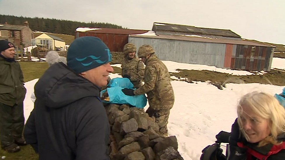 Residents receive supplies from soldiers
