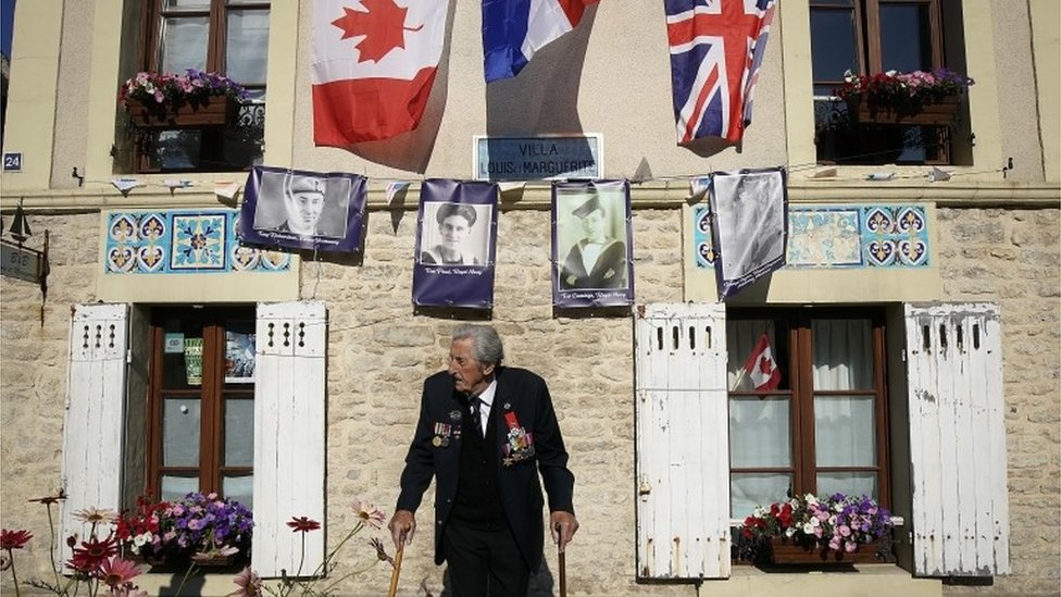 D-Day landing craft veteran, Ted Emmings, aged 94, of The Royal Navy, walks past a villa in Arromanches that has been decorated and is adorned with a photograph of him and other veterans