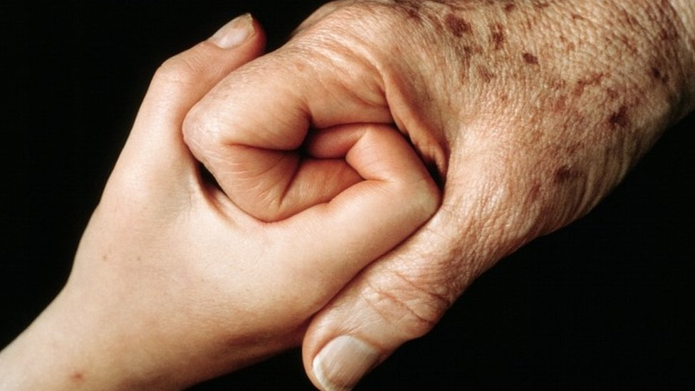 Young person and elderly person holding hands