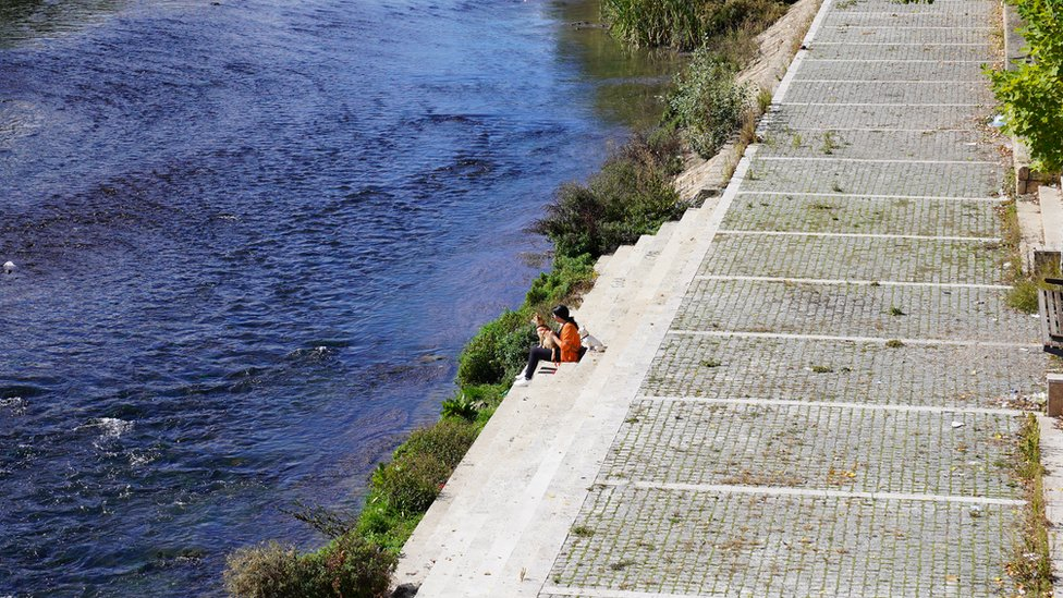 """Iako barikade na mostu i podsećaju na turbulentna vremena u Mitrovici, danas Mitrovčani na Ibar """"beže"""" od svakodnevnice, a u ovom slučaju i od predizobrne kampanje"""