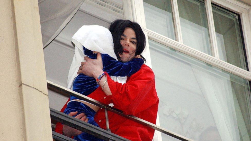 Michael Jackson con su hijo en un balcón.