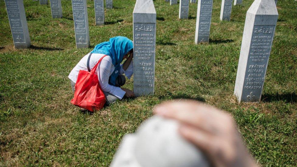 Una mujer bosnia junto a la tumba de un familiar en el cementerio donde reposan las víctimas de la masacre de Srebrenica.