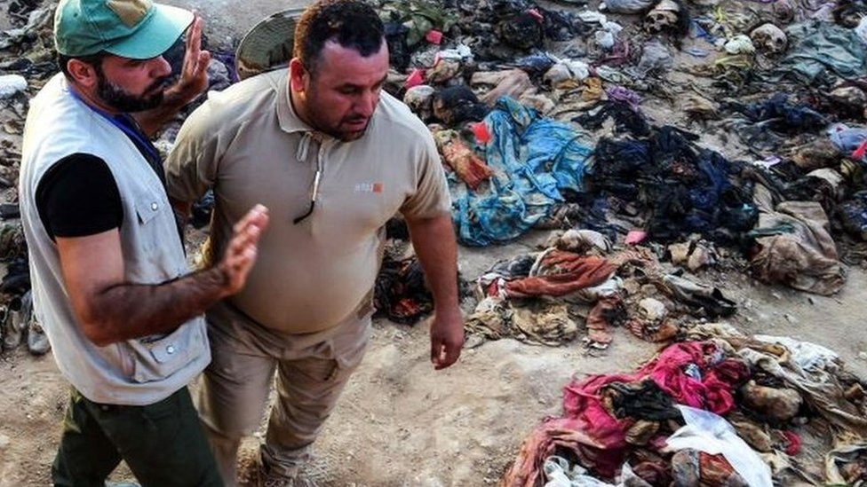 Médicos forenses en una fosa común en Tal al-Sheikhiya.
